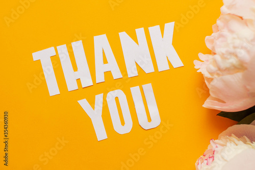 Photo peonies with paper words. Thank you on orange paper