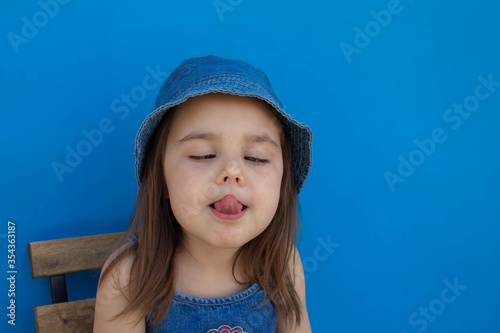 Fényképezés A girl in a Panama hat grimaces and shows her tongue against a blue isolated bac
