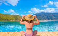 Young Girl In Hat Sunbathes On A Wooden Pier And Summer Landscape On The Sea - Oludeniz Beach And Blue Lagoon, Oludeniz Beach Is Best Beaches In Turkey - Fethiye, Turkey