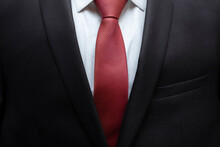 Closeup Of Black Business Suit With White Shirt And Red Tie. Businessman In A Black Suit With A Red Tie. Business Concept.