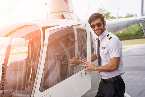 Handsome Pilot Smiling While Opening the Door of the Helicopter. Fototapet