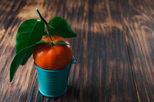 Fresh Tangerines With Leaves In A Bucket On A Wooden Old Background