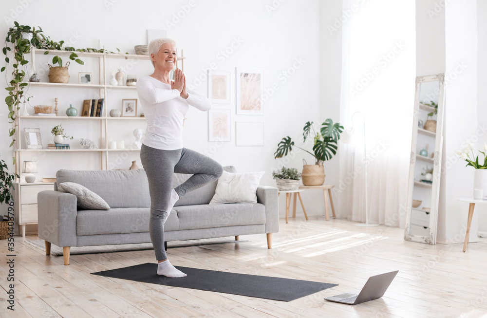 Fototapeta Sporty Senior Woman Practicing Yoga With Online Tutorials At Home