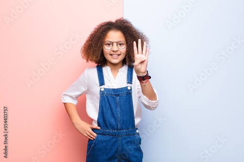 Fotomural african american little girl smiling and looking friendly, showing number four o
