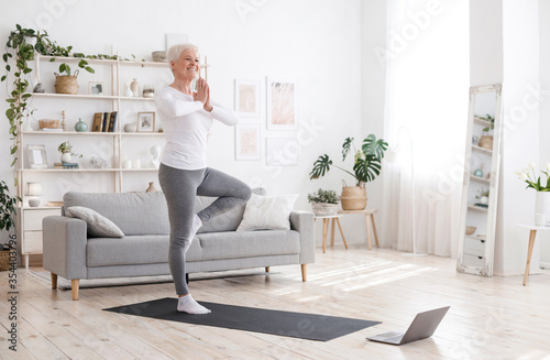 Obraz Sporty Senior Woman Practicing Yoga With Online Tutorials At Home - fototapety do salonu