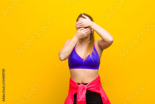 young blonde woman covering face with both hands saying no to the camera! refusing pictures or forbidding photos Fototapeta
