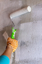Cement Wall Painting With White Paint And Roller. Yellow Gloves.