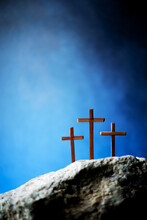 Three Wooden Cross On Calvary Hill, Blue Background. Crucifixion, Resurrection Of Jesus Christ. Christian Easter Holiday, Golgotha. He Risen And Alive. Jesus Is The Reason. Gospel, Salvation Concept
