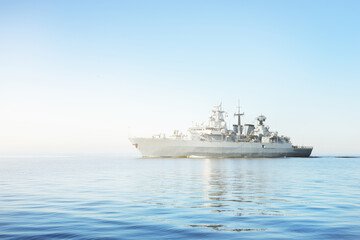 Large grey modern warship sailing in still water. Clear blue sky. Baltic sea, Germany. Global communications, international security theme