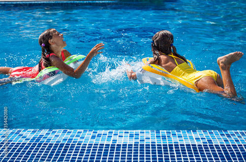 Photo Two tween girls playing, splashing, laughing and have fun in the blue water of swimming pool with inflatanle rings
