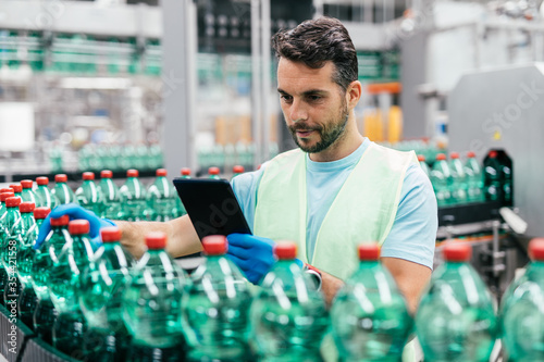 Vászonkép Male worker in bottling factory checking water ottles before shipment
