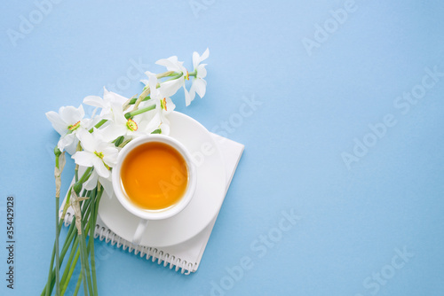 Obraz na plátně Cup of yellow tea, notebook and a bouquet of whitevnarcissus on a blue backgroun