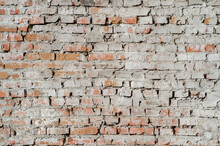 Old Red Brick Wall With Remnants Of Plaster And Gray Cement. Background