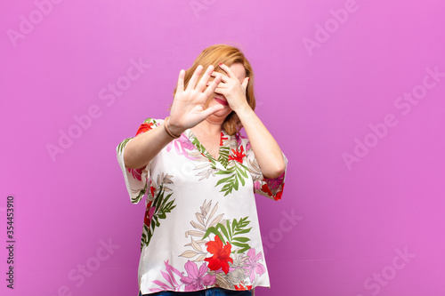 Fotografie, Tablou middle age woman covering face with hand and putting other hand up front to stop