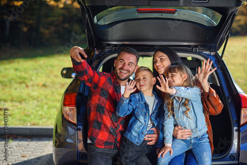 Happy stylish parents with their cute lovely children are making funny selfie on smart phone while sitting in the trunk Wallpaper Mural