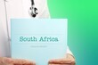 canvas print picture - South Africa. Doctor (male) with stethoscope holds medical report in his hands. Cutout. Green turquoise background. Text is on the documents. Healthcare/Medicine