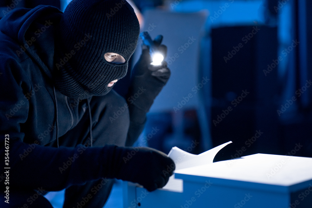 Fototapeta Masked intruder holding and reading confidential documents