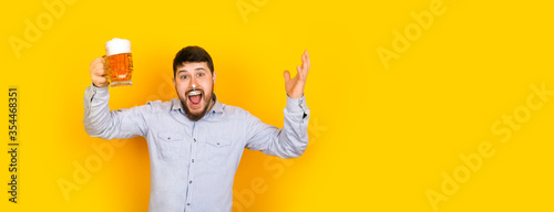 Foto funny man with a glass of beer and foam on his mustache and nose on a yellow bac