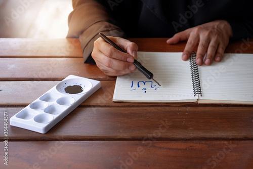 Arab Muslim woman writing Arabic handwriting with ink, Arabic letters mean the n Wallpaper Mural