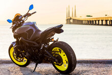 A Black Motorbike Parking By The Shore Of Penang Bridge