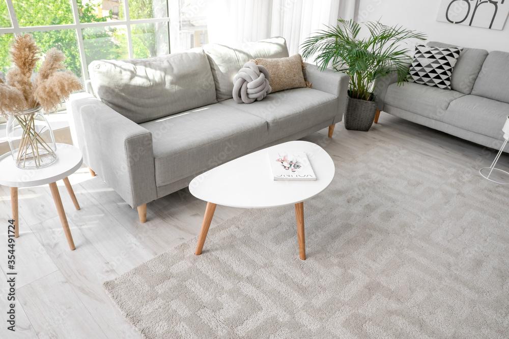 Fototapeta Stylish interior of living room with carpet and sofas