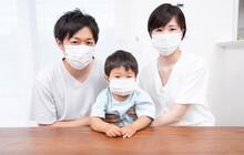 室内でマスクをする3人家族