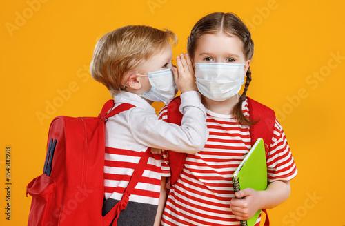 Obraz Children in masks gossiping during break in studies. - fototapety do salonu