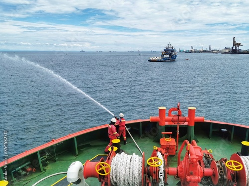 Fotografie, Obraz Marine crew conducting fire drill and tested fire hydrant pump on board a marine offshore vessel