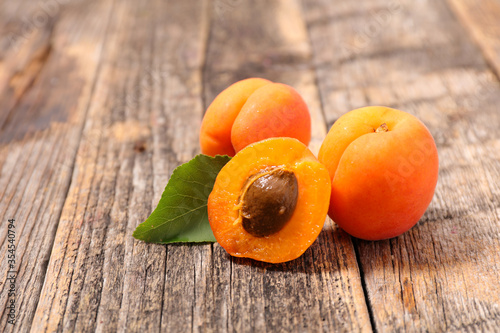 Fotografiet fresh apricot and leaf on wood background