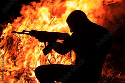 Vászonkép protester shoots from ak amid a burning car