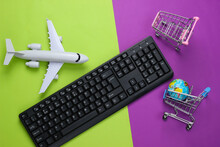 Air Delivery. Global Supermarket. Online Shopping. Shopping Trolleys With Globe, Keyboard, Airplane Figurine On Purple Green Background. Top View. Flat Lay
