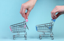 Shopping Concept. Hands Holding Supermarket Trolley On A Blue Background.