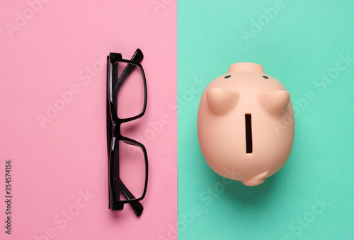 Piggy bank and glasses on pink blue background Fotobehang
