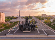 View From Above Through The Sculpture Of The Goddess Nika In A Chariot With Six Horses On The Roof Of The Arc De Triomphe In Moscow At Victory Park And City Streets At Sunset, Aerial Photo