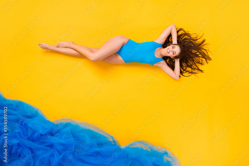 Fototapeta Top view above high angle flat lay flatlay lie concept full length body size view of attractive fit cheerful girl taking sun bath plage isolated on bright vivid shine vibrant yellow color background
