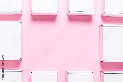 Fototapeta Lot of square carton boxes on pink background obraz