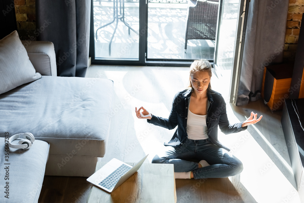 Fototapeta attractive young woman with closed eyes sitting in lotus pose near laptop