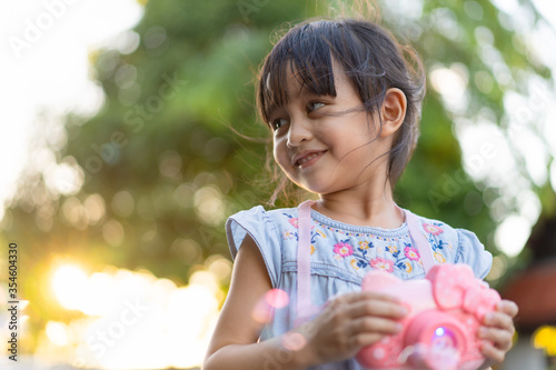 Obraz Beautiful 4 years old asian little girl is smiling with happy moment while she is playing bubbles outdoor. - fototapety do salonu