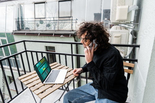 Man talking on smartphone near laptop with sports bet website on balcony Canvas Print