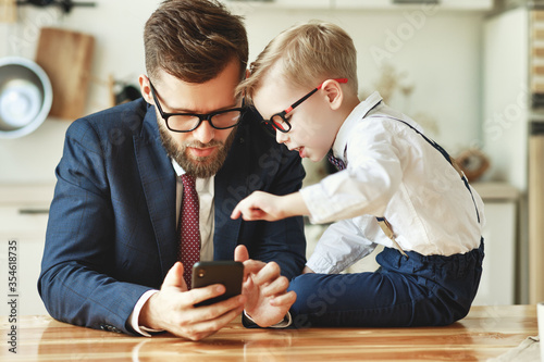 Fototapeta businessman father with a young schoolboy son looking at a smartphone. obraz