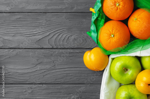 Obraz Apples and oranges in packets on black wooden table - fototapety do salonu
