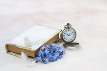 Forget Me Nots In A Book, Pocket Watches, Feathers And A Porcelain Figurine Of A Bird