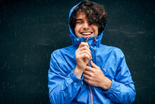 Portrait Of The Man Smiling Broadly, Wearing Blue Raincoat During Rain Outside. Handsome Male In Blue Raincoat Enjoying The Rain On Black Wall. Young Man Has Joyful Expression In Rainy Weather.