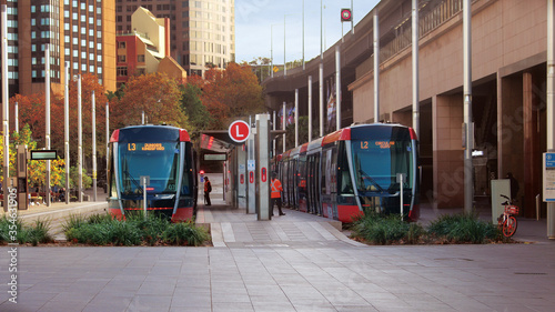 Obraz Streetscape outside Circular quay light rail station. Pictured are two light rail trains. - fototapety do salonu