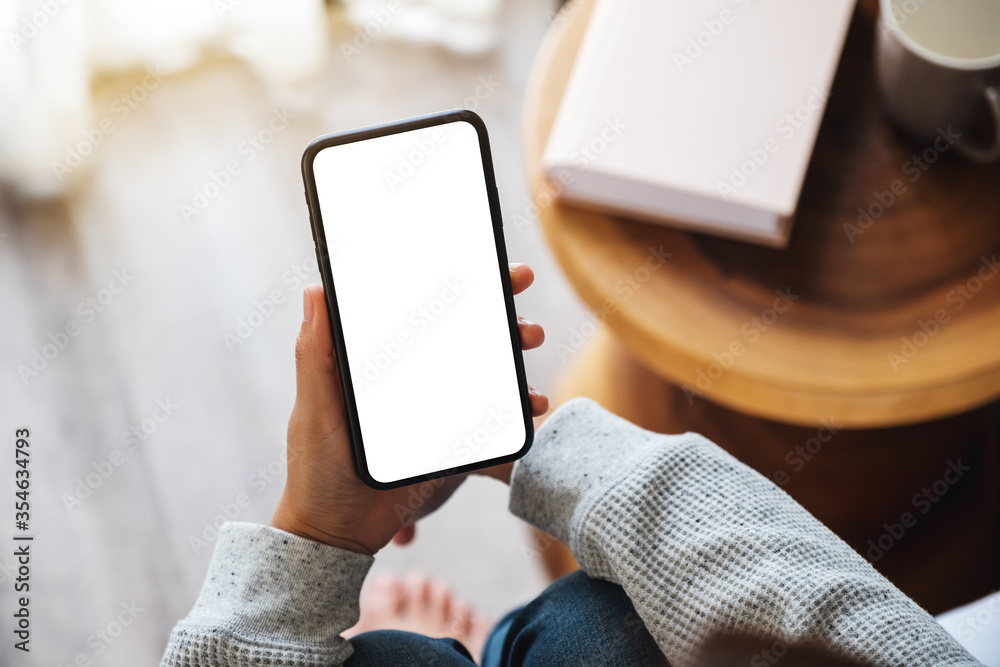 Fototapeta Top view mockup image of a woman holding mobile phone with blank desktop screen while sitting in bed room at home