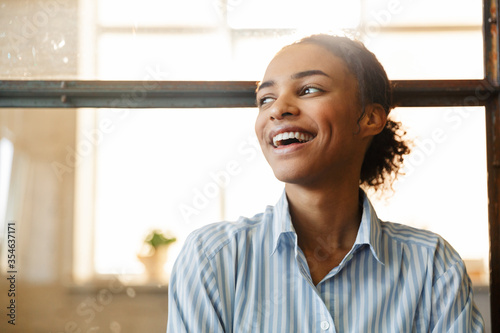 Obraz Photo of joyful african american woman smiling while leaning on wall - fototapety do salonu