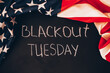 Blackout tuesday inscription on a black background with american flag around. Black lives matter, blackout tuesday2020 concept.