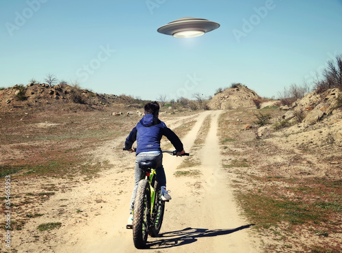 A boy riding a bicycle following a UFO фототапет