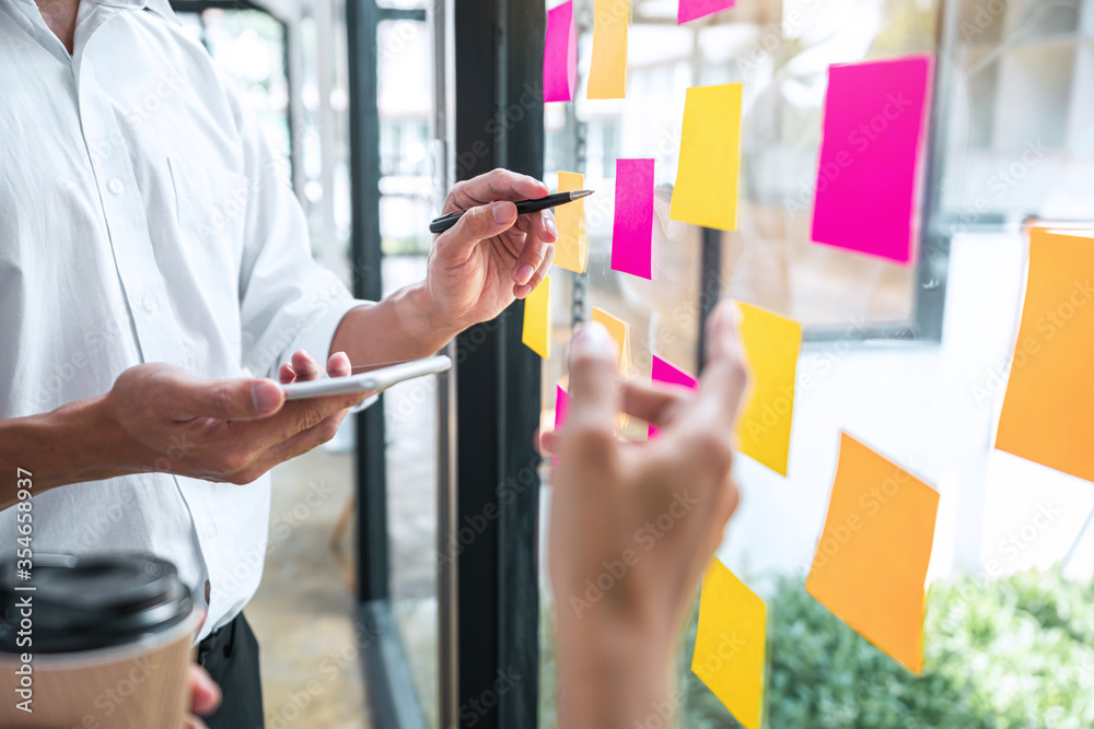 Fototapeta Creative team using post it notes in glass wall to writing strategy