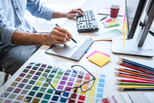 Fototapeta Image of male creative graphic designer working on color selection and drawing on graphics tablet at workplace with work tools and accessories in workspace obraz